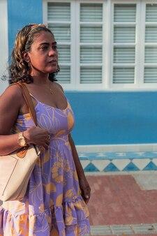 通りを歩いてドレスとハンドバッグの魅力的な40歳の女性
