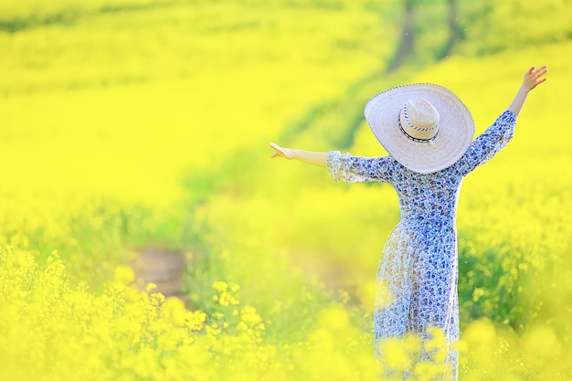 Attractive active beautiful female, freedom happy view from the back, in a field of flowers