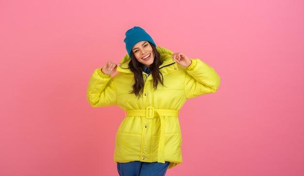 明るい黄色のカラフルな冬のダウンジャケット、暖かいコートのファッショントレンドでピンクの壁にポーズをとる魅力的なアクティブな女性モデル