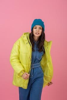 Привлекательная активная модель женщины позирует на розовой стене в красочном зимнем пуховике ярко-желтого цвета, теплой тенденции моды пальто