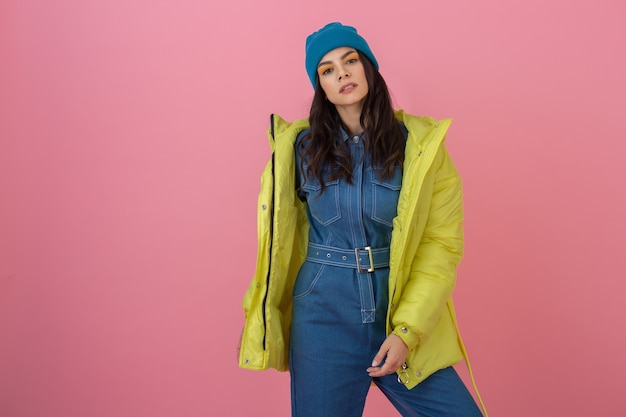 Attractive active woman model posing on pink wall in colorful winter down jacket of bright yellow color, warm coat fashion trend