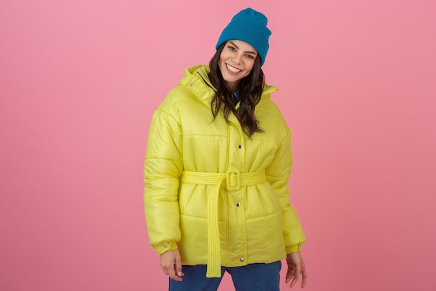 明るい黄色のカラフルな冬のダウンジャケットでピンクの壁にポーズをとる魅力的なアクティブな女性、笑顔の楽しみ、暖かいコートのファッショントレンド、クレイジーショックを受けた驚きの表情