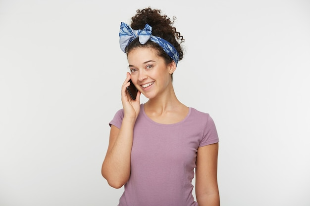 Attractive adorable brunette woman with curly hair in casual t-shirt and headband, talking with someone special on phone