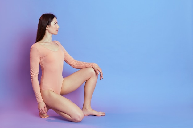 Attractive adorable female wearing beige bodysuit sitting on knee and looking away, has confident look and perfect body, poses isolated over blue wall.