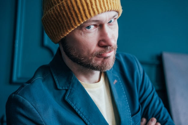 Attractive adult bearded man hipster in yellow hat looks into camera and smiles slyly
