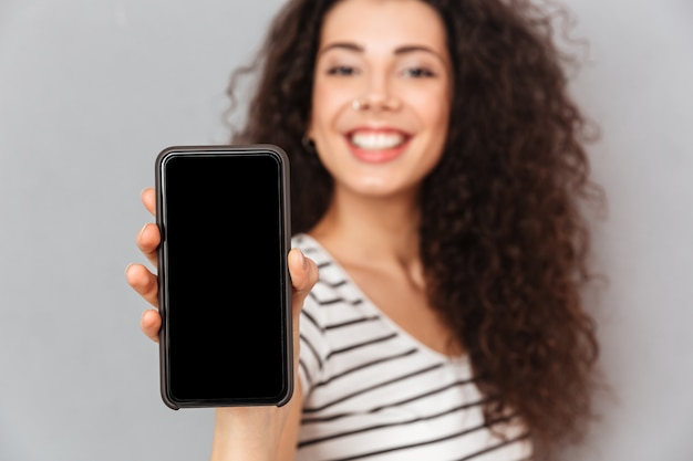 Attractive adult girl with ring in nose demonstrating her mobile phone advertising new model being glad while isolated against grey wall