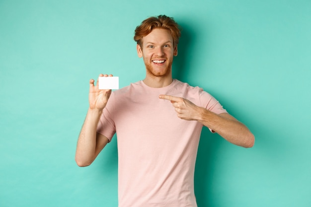 수염과 빨간 머리를 한 매력적인 성인 남성이 플라스틱 신용 카드를 손가락으로 가리키며 카메라를 보고 기뻐하며 청록색 배경 위에 서 있습니다.