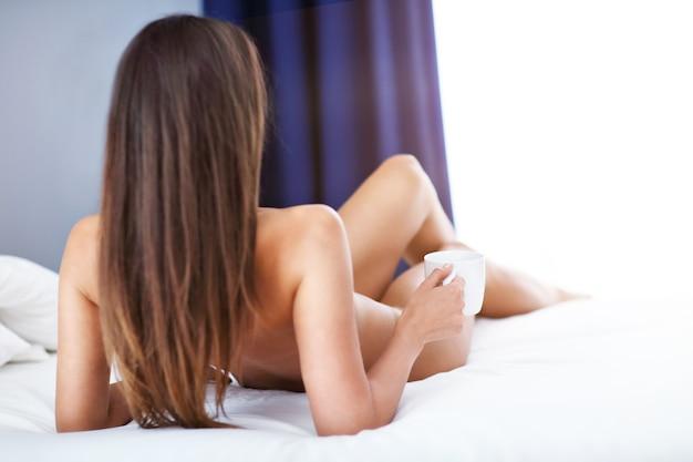 朝、ベッドに横たわる魅力的な大人の裸の女性