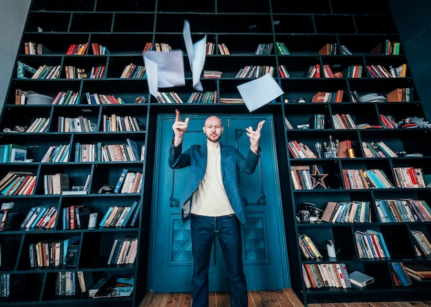 Attractive adult successful bald bearded man in suit throwing documents at camera