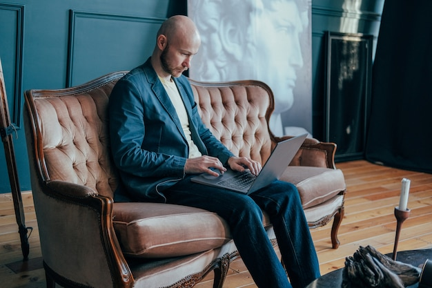 Attractive adult successful surprised bald man with beard in suit working at laptop