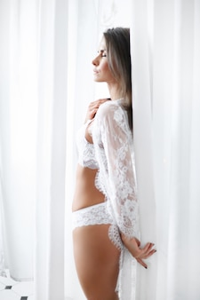 Attractive adult woman in erotic white lingerie