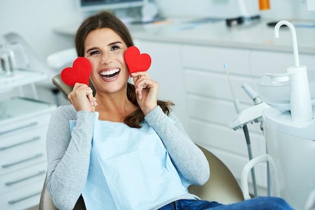 Привлекательная взрослая женщина в офисе стоматолога с сердечками