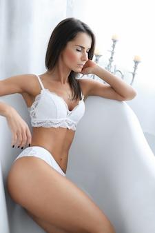 浴槽の中のエロティックな白いランジェリーの魅力的な大人の女性