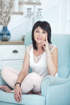 Attractive adult woman sitting on the couch indoors. beautiful middle-age female at home.