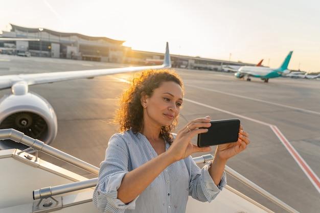 飛行機で飛ぶ前に自分撮りをする魅力的な大人の女性