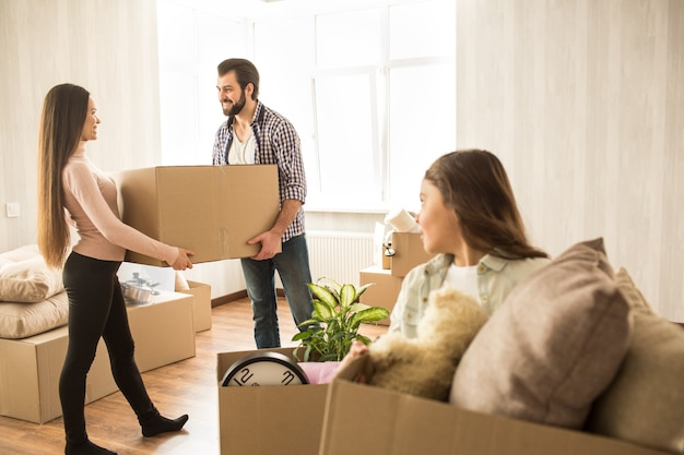 매력적인 성인은 거실을위한 물건 상자와 함께 서서 서로를보고 웃고 있습니다.