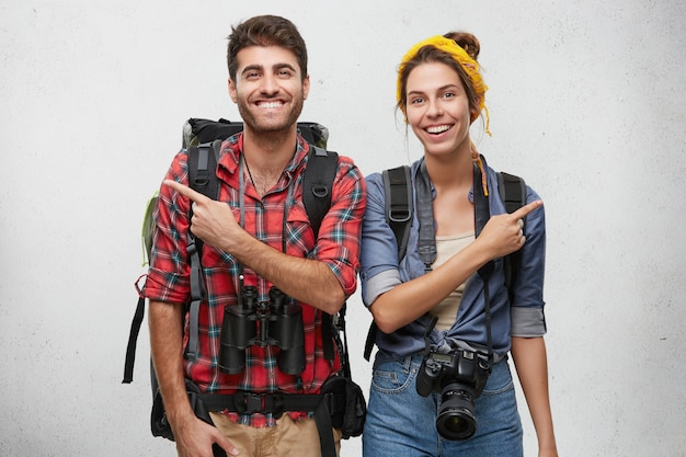 Attractive adventurous young couple in love wearing practical clothes, carrying rucksacks, photo camera and binoculars having cheerful looks, pointing fingers in opposite directions
