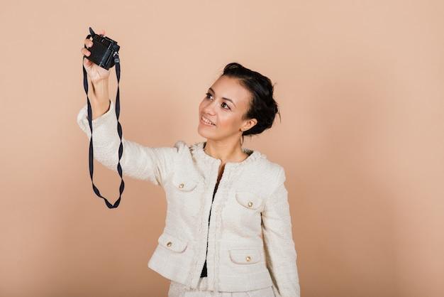 スタジオで写真を撮る一眼レフデジタルカメラを使用して、魅力的なアフリカ系アメリカ人の黒人女性。写真の学生と観光のライフスタイル。
