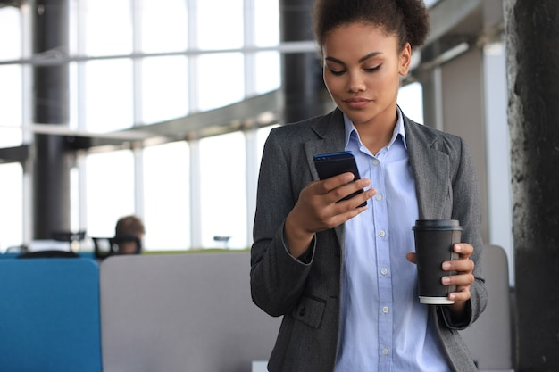 Attractive african american business woman using mobile phone while standing in creative office.