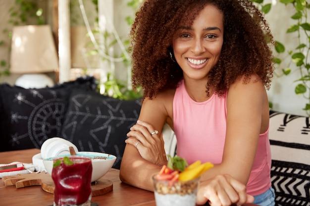 ピンクのtシャツに身を包んだ魅力的なアフリカ系アメリカ人の暗い肌の女性は、カクテルと甘いデザートに囲まれたカフェのテーブルで交差した手に座って、表情を喜ばせ、休息をとっています。