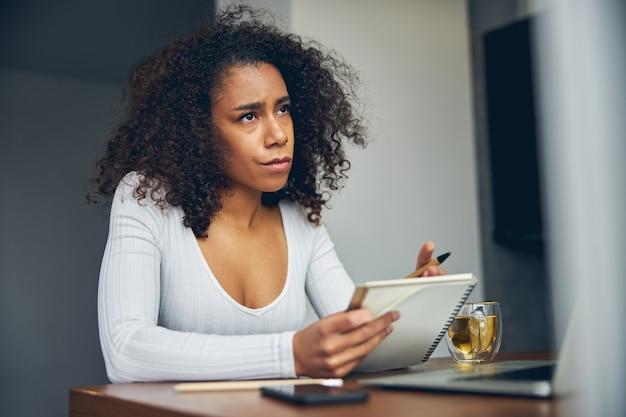 그녀의 노트와 함께 작업하는 동안 앉아서 생각하는 캐주얼 옷에 매력적인 아프리카 계 미국인 여성