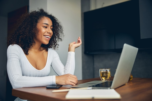 차와 함께 컴퓨터 앞에 앉아 작업하는 동안 웃 고 매력적인 흑인 여성