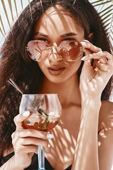 目をそらしながらカクテルを保持しているスタイリッシュなサングラスで魅力的なアフリカ系アメリカ人の女の子。ヤシの葉の影が彼女の体にあります。夏には、コンセプトをリラックスしてください。閉じる
