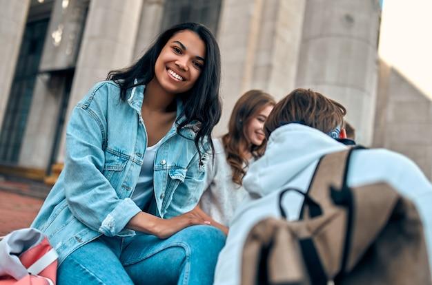 Привлекательная афро-американская студентка сидит на ступеньках возле кампуса со своими друзьями.
