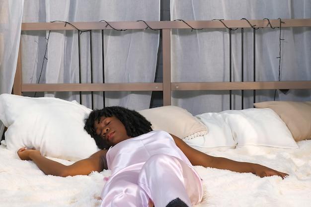 곱슬머리를 한 매력적인 아프리카계 미국인 소녀는 큰 침대에 누워 세련된 침실에서 갑자기 깨어납니다