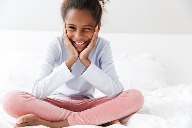 Привлекательная афро-американская маленькая девочка улыбается, сидя в постели у себя дома