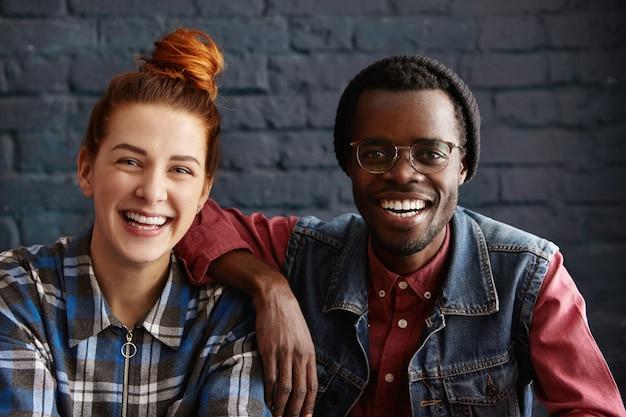 帽子とメガネの美しい若い赤毛の肩に腕を休んで魅力的なアフリカ系アメリカ人男性