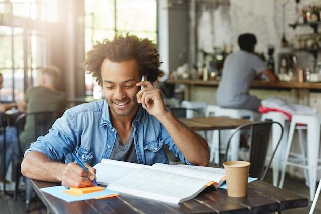 Attraente studente afroamericano facendo compiti a casa alla mensa universitaria, seduto al tavolo con un libro di testo e una tazza di caffè, prendendo appunti e parlando al cellulare, con sguardo felice
