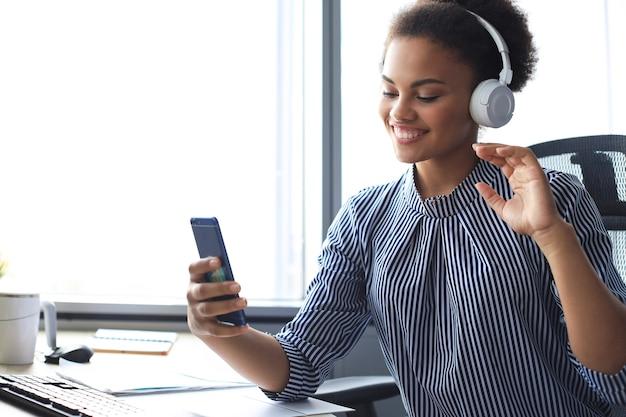 이어폰에 앉아있는 동안 휴대 전화에 영상 통화를 하는 매력적인 아프리카계 미국인 여자.