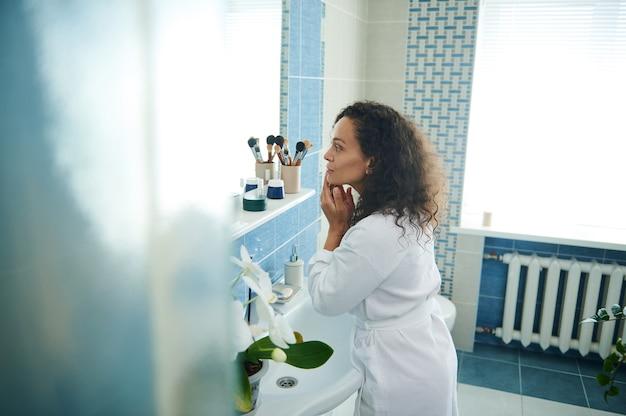흰색 목욕 가운을 입은 매력적인 아프리카계 미국인 여성이 거울에 비친 자신의 얼굴을 살펴봅니다