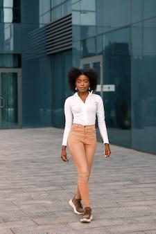 魅力的なアフリカ系アメリカ人の女性が建物の近くを歩く