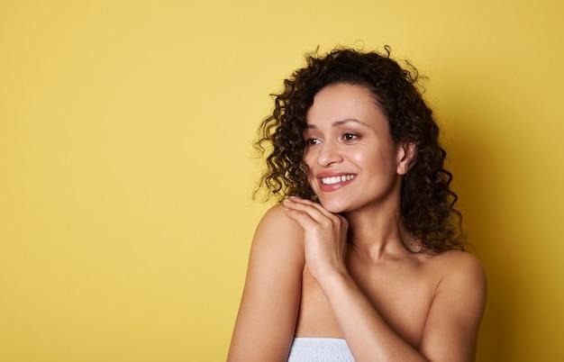 目をそらし、歯を見せる笑顔で笑っている巻き毛の魅力的なアフリカ系アメリカ人の若い女性。コピースペース