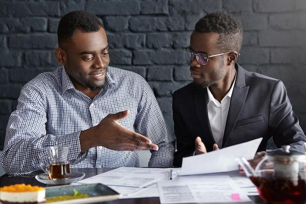 Attraente uomo d'affari africano in bicchieri e tuta in possesso di documenti