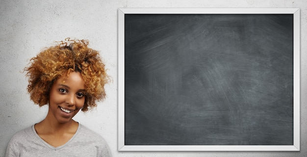 Attractive african college student with facial piercing presenting her project to class standing at blank blackboard.