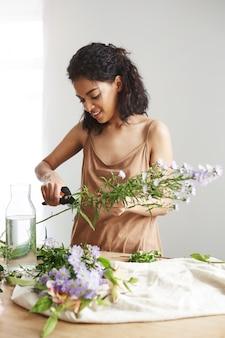 魅力的なアフリカの女性花屋切削茎で職場。白い壁。