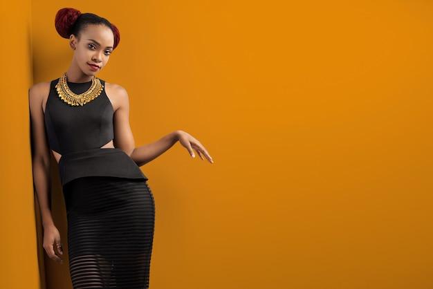 Attraente donna africana che indossa un elegante abito nero in posa sul muro
