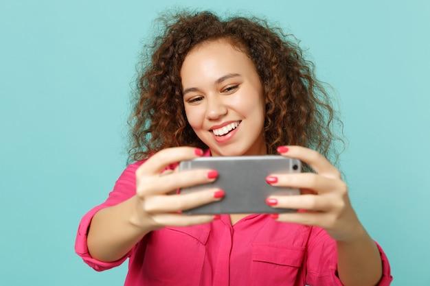 スタジオで青いターコイズブルーの壁の背景に分離された携帯電話でselfieショットをしているピンクのカジュアルな服を着た魅力的なアフリカの女の子。人々の誠実な感情、ライフスタイルのコンセプト。コピースペースをモックアップします。