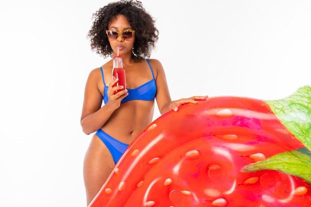 青い別の水着で魅力的なアフリカの女性が水泳マットレスを保持し、白い壁にカクテルを飲む