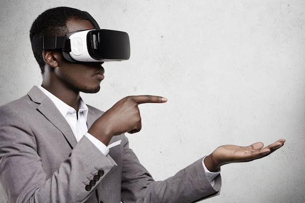 Attractive african man in formal wear and 3d glasses pointing his fingers at copy space above his open palm as if using some gadget.