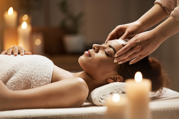 Attractive african woman enjoying face massage in spa salon.