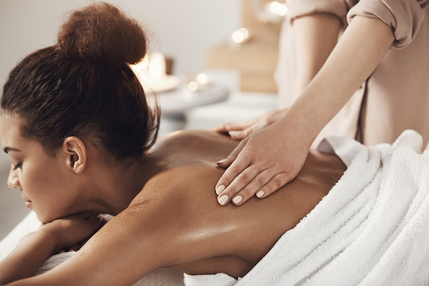 Attractive african woman having massage relaxing in spa salon. closed eyes.