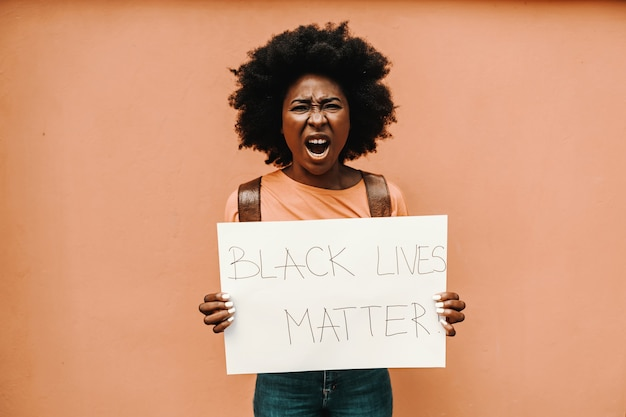 Black lives matterで紙を持っている魅力的なアフリカの女性!と叫んで。