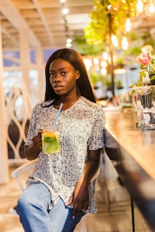 카페에 앉아서 신선한 레모네이드를 마시는 매력적인 아프리카 여자.