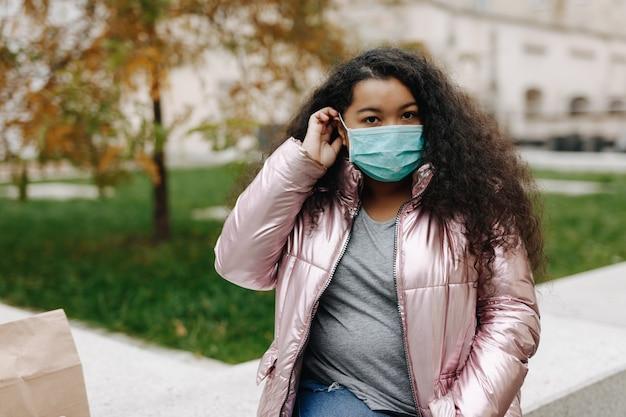 路上でポーズをとる医療フェイスマスクの魅力的なアフリカの女性。コロナウイルスからの保護。パンデミックの時間と検疫。