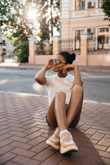 日没の街通り広場に座っている魅力的なアフロアメリカンの女性