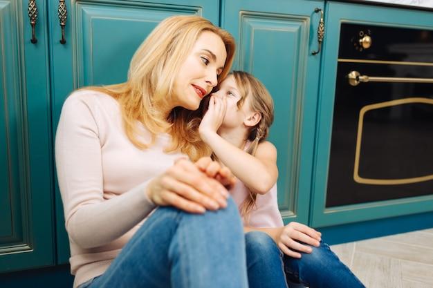 魅力的なアラート金髪の母と娘が笑顔でキッチンの床に座って、女の子が彼女の耳にささやきます